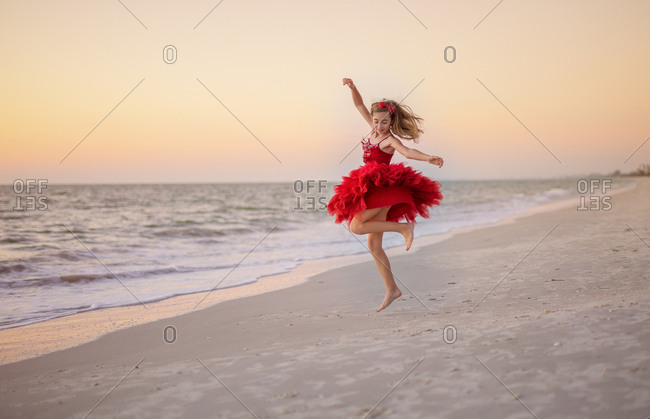 Young caucasian girl dancing and twirling on beach in a red dress