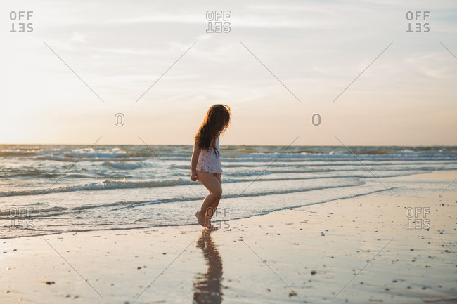 Young caucasian girl on the beach at sunset walks in the low tide
