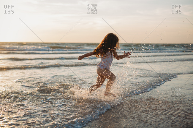 Child splashing and running in the surf along the beach in Florida