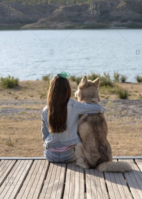 Girl relaxing with her pet husky by a lake watching the sun go down