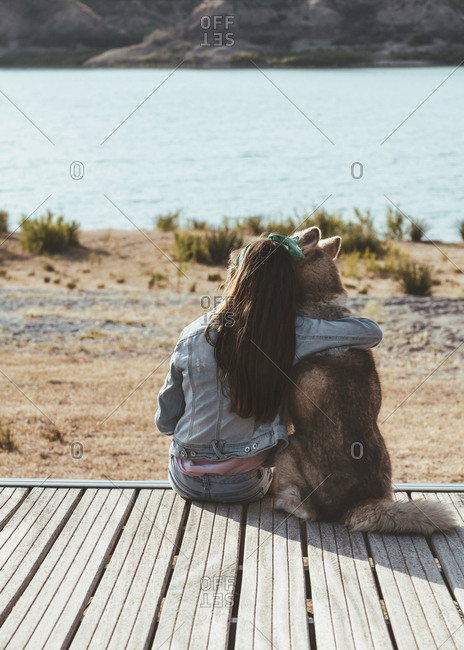 Girl sat by a lake hugging her pet husky watching the sunset