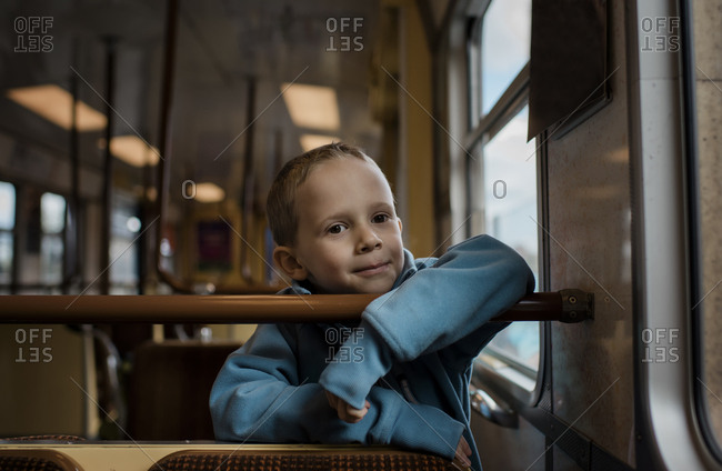 Young boy sat on a train smiling