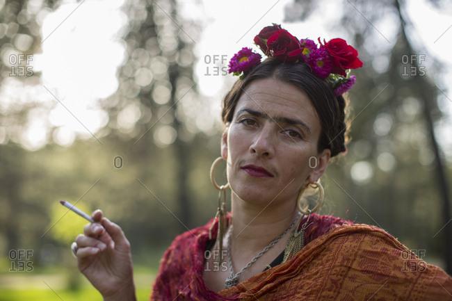 Portrait of woman smoking dressed up like the artist Frida Kahlo