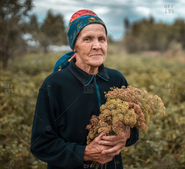 Senior woman with bouquet of edible plant dill herb