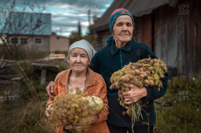 Two Russian old women are standing with dill herbs in hands