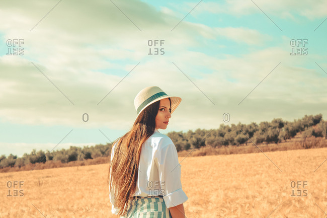 A young girl walking through a wheat field during a sunny spring day