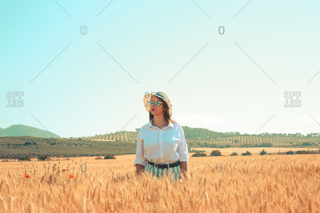 A young woman stay in the middle of a wheat field