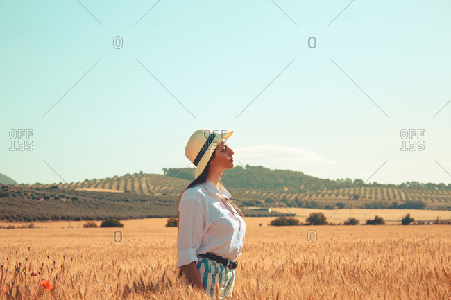 A girl standing in a wheat field enjoying a sunny day in Spain