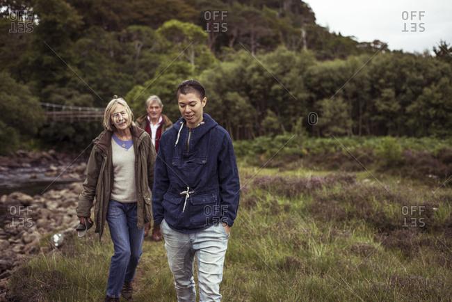 Mixed race older family walks along wild river grass