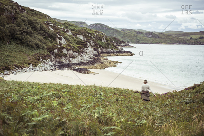 Woman walks through high grass ferns to remote untouched beach