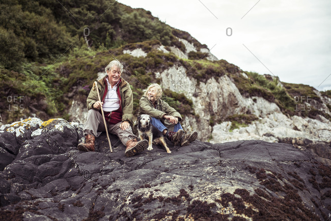 Retired couple sit with dog on rocks by ocean in rugged Scotland