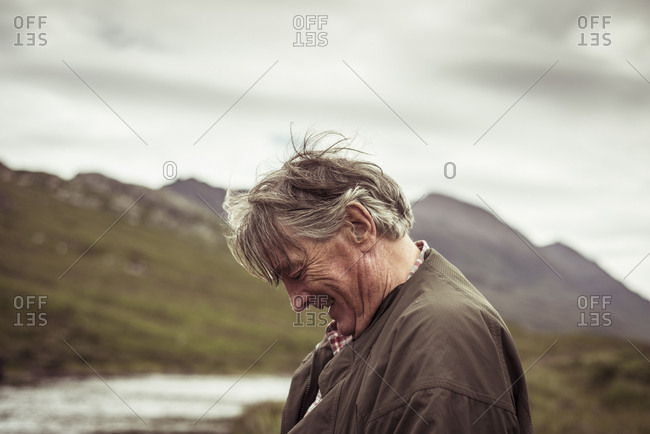Retired man laughs and smiles out fishing in remote river mountain