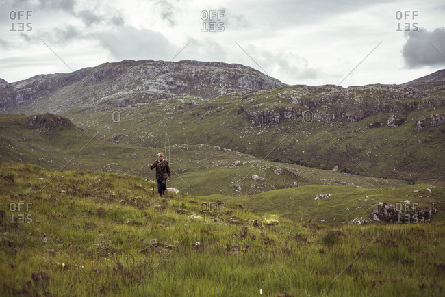 Retired man walks along in remote mountains on fishing trip