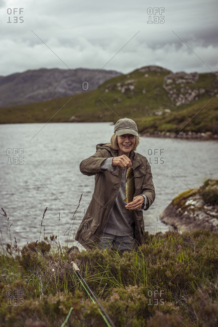 Retired woman holds wild trout from caught from loch in Scotland
