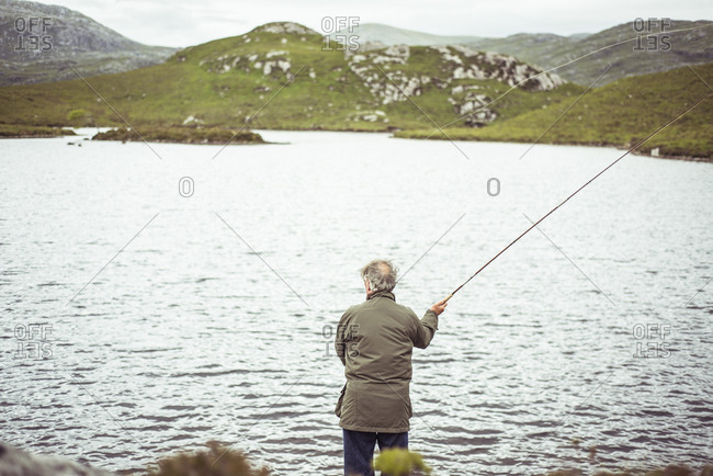 Man fly fishing by loch in remote mountains in Scotland