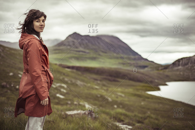 Young woman stands on mountain looking at view of loch in Scotland