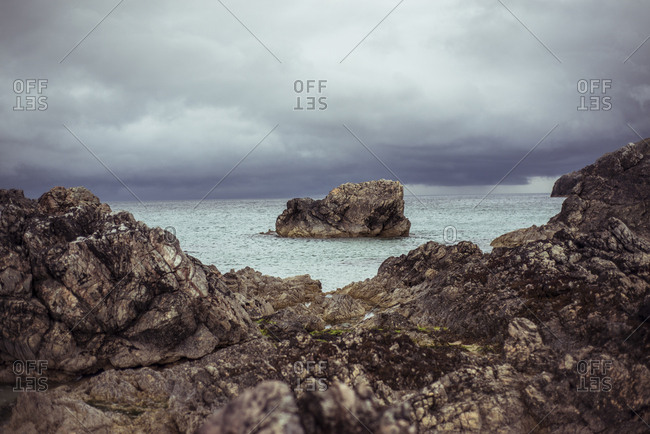 Rock sits in ocean framed by cliffs and clouds