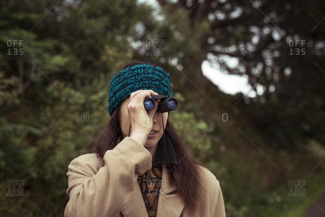 Girl in beanie looks through binoculars at view