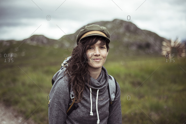 Girl in hat and back pack smiles while trekking through mountains