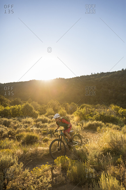 A woman riding a mountain bike outdoors just before sunset.