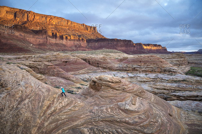 Woman hiking in a dramatic desert landscape at sunrise.