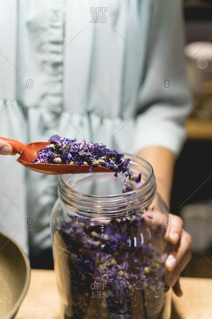 Young woman with shovel and dried flowers