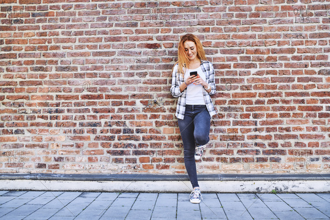 Young woman leaning against brick wall in the city while using smartphone