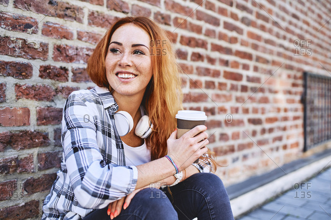 Young woman sitting against brick wall holding cup of coffee and looking away