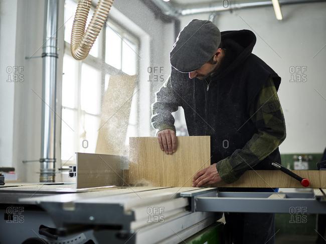 Carpenter sawing wood with circular saw