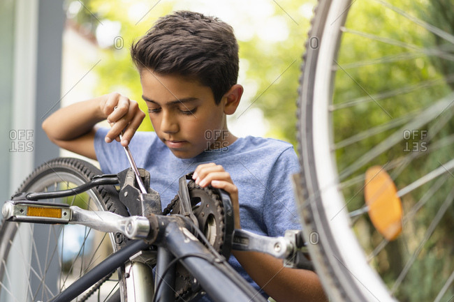 Boy repairing his bicycle