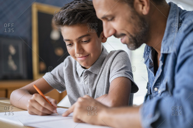 Smiling father helping son doing homework