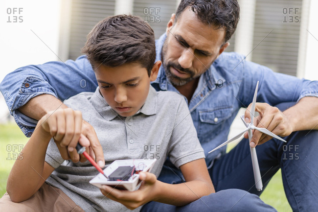 Father and son assembling a wind turbine model construction kit in garden