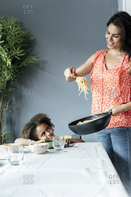 Mother serving pasta meal for daughter sitting at dining table