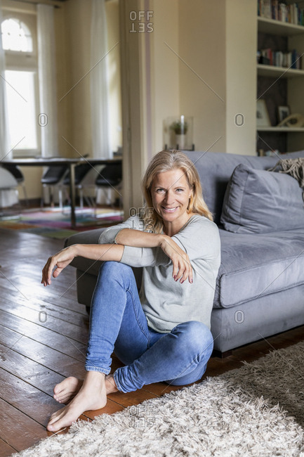 Portrait of smiling mature woman siiting barefoot on the floor in the living room