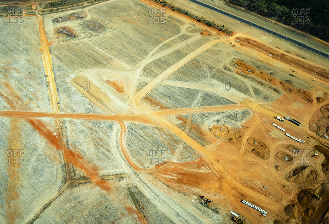 Aerial view of a quarry with trucks moving orange sand in Queensland- Australia