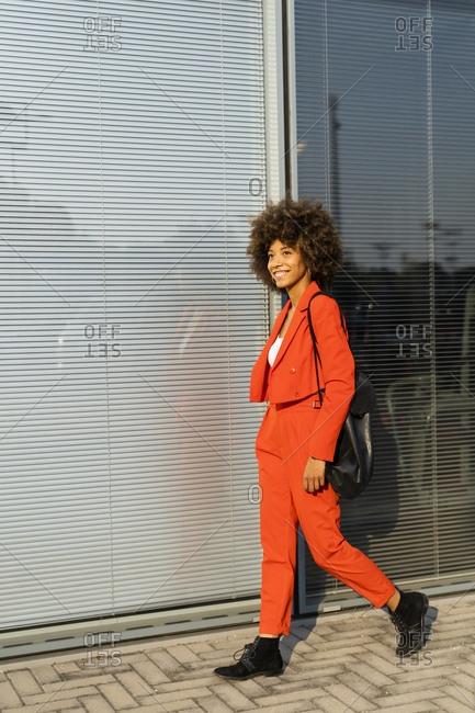 Smiling young woman with shoulder bag wearing fashionable red pantsuit