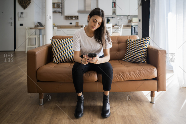 Young woman on couch at home using cell phone