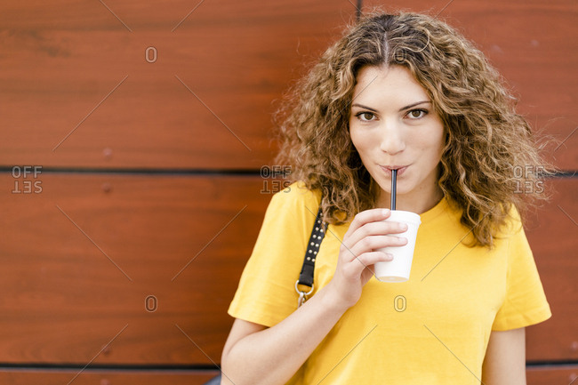 Portrait of young woman drinking from disposable cup