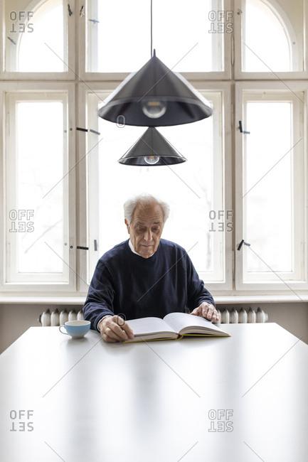 Senior man reading book at table at home