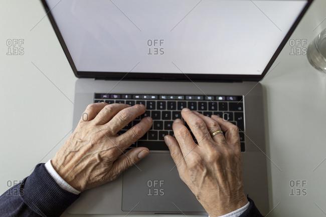 Close-up of senior man using laptop