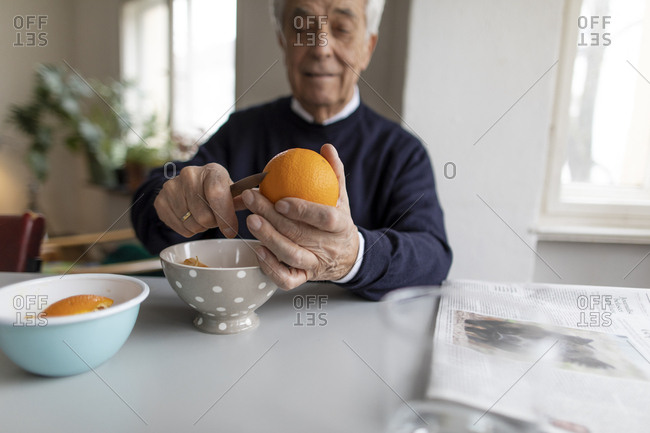 Senior man peeling orange at home
