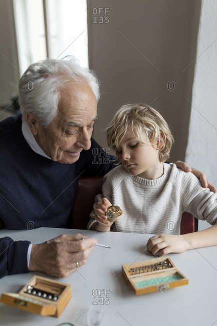 Watchmaker and his grandson examining watch together