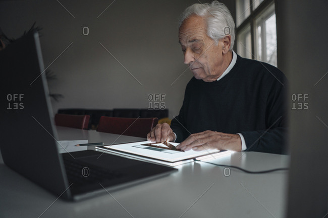 Senior man using tablet with architectural plan