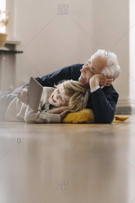 Happy grandfather and grandson lying on the floor at home using a tablet