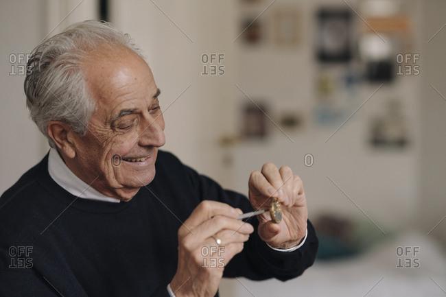 Smiling senior man repairing a watch at home