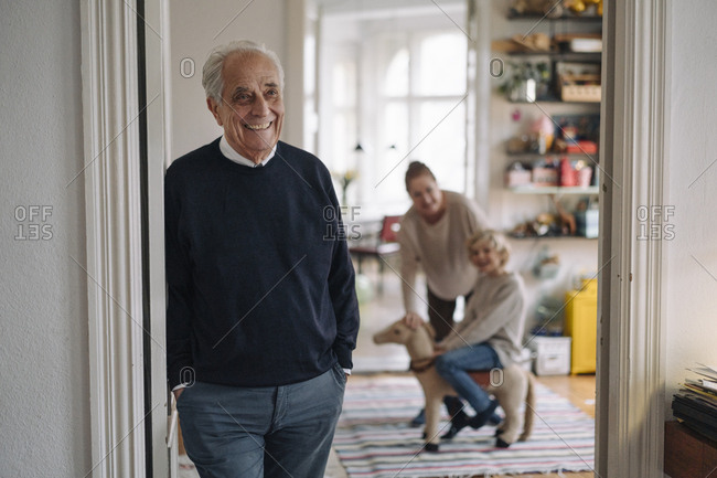 Happy grandfather with wife and grandson in background at home