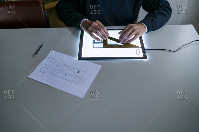 Close-up of senior man using ruler and tablet with architectural plan