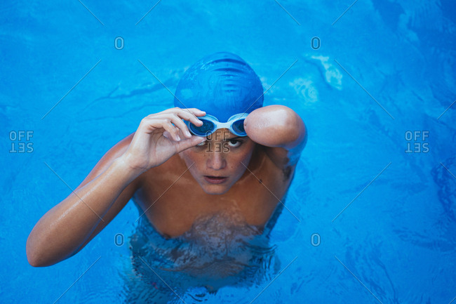 Portrait of young paralympic swimmer putting on swimming goggles