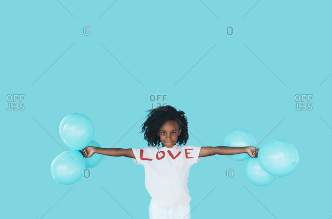 Little girl In front of a blue wall- holding balloons