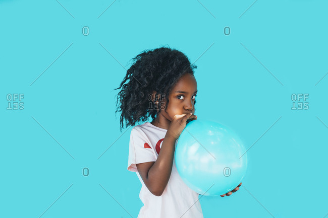 Little girl In front of a blue wall- blowing up balloon